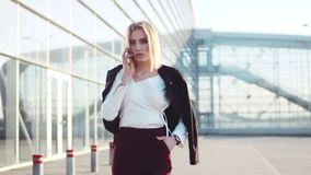 De mooie blondevrouw in modieuze uitrustingspassen door de de de luchthaventerminal, wijzerplaten en besprekingen op de telefoon, stock video
