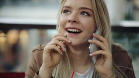 De mooie blondevrouw spreekt op de telefoonzitting in het restaurant en het drinken van een milkshake stock footage