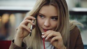De mooie blondevrouw spreekt op de telefoonzitting in het restaurant en het drinken van een milkshake stock videobeelden