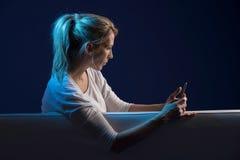 De mooie blondevrouw zit op bank, en gebruikt haar cellphone Stock Afbeelding
