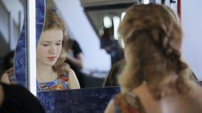 De mooie blondevrouw zit voor spiegel en spreekt met haar vrienden stock footage
