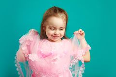 De mooie boord van het de holdingskant van het kindmeisje van haar roze kleding op geïsoleerd blauw royalty-vrije stock foto