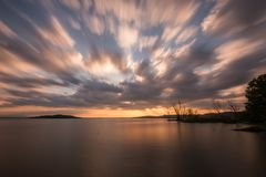 De mooie brede hoek, lange blootstellingsmening van een meer bij zonsondergang, met een reusachtige hemel met zich het bewegen be royalty-vrije stock afbeeldingen