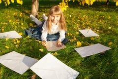 De mooie brief van de meisjeslezing terwijl het zitten Stock Foto