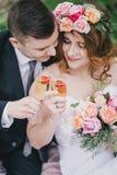De mooie bruid in een huwelijkskleding met boeket en van de rozenkroon het stellen met bruidegom die huwelijk dragen past aan Royalty-vrije Stock Foto