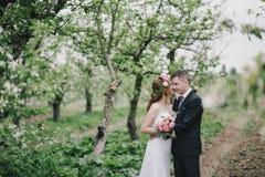 De mooie bruid in een huwelijkskleding met boeket en van de rozenkroon het stellen met bruidegom die huwelijk dragen past aan Royalty-vrije Stock Afbeelding