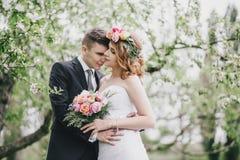 De mooie bruid in een huwelijkskleding met boeket en van de rozenkroon het stellen met bruidegom die huwelijk dragen past aan Royalty-vrije Stock Fotografie
