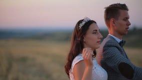 De mooie bruid en de bruidegom lachen en de slagzeepbels in het park bij zonsondergang stock footage