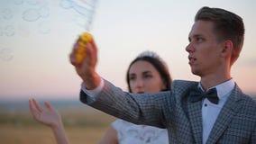 De mooie bruid en de bruidegom lachen en de slagzeepbels in het park bij zonsondergang stock videobeelden