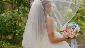 De mooie bruid stelt met huwelijksboeket stock footage