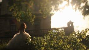 De mooie bruid in witte toga loopt met haar knappe bruidegom aan romantisch uitstekend paleis in warme zonsondergangstralen stock video
