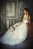 De mooie bruid zit als leervoorzitter in een donkere ruimte Stock Foto's