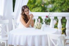 De mooie bruid zit bij een lijst in een comfortabele koffie, zette een wit boeket van rozen op een lijst en bekijkt het huwelijks royalty-vrije stock afbeelding