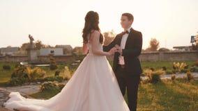 De mooie bruidegom komt aan bruid en streelt haar bij kasteel stock footage