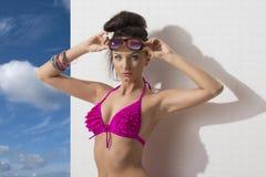 De mooie brunette met bikini, kijkt binnen aan de lens Stock Afbeeldingen