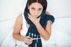De mooie caucasainvrouw ligt in bed en neemt pil Stock Foto