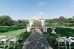 De mooie ceremonie van het de zomerhuwelijk in openlucht Verfraaide stoelentribune op het gras Huwelijksboog die van lichte doek  Royalty-vrije Stock Foto's