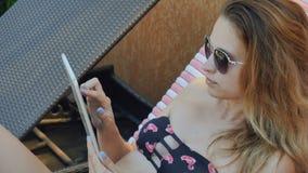 De mooie dame in bikini gebruikt tablet het ontspannen op ligstoel stock video