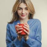 De mooie dame in blauw overhemd drinkt thee Stock Afbeelding