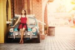 De mooie dame die van Azië zich dichtbij retro auto bevinden Royalty-vrije Stock Foto