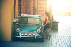 De mooie dame die van Azië zich dichtbij retro auto bevinden Stock Afbeelding