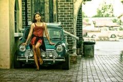 De mooie dame die van Azië zich dichtbij retro auto bevinden Royalty-vrije Stock Foto's