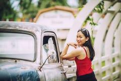 De mooie dame die van Azië zich dichtbij retro auto bevinden Stock Afbeeldingen