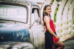 De mooie dame die van Azië zich dichtbij retro auto bevinden Royalty-vrije Stock Fotografie