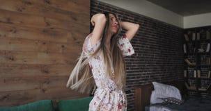 De mooie dame die van het blondehaar in de ochtend modieuze pyjama's dragen die voor de camera dansen heeft een grote stemming en stock videobeelden