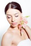 De mooie dame met lilly bloeit Perfecte huid royalty-vrije stock afbeelding