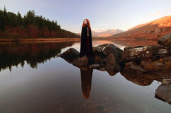 De mooie dame met rood haar, die een zwarte mantel dragen, dacht in de nog wateren van een meer na royalty-vrije stock fotografie