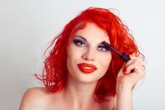 De mooie dame van de meisjesvrouw, die mascara op haar lange wimpers toepassen stock afbeeldingen