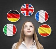 De mooie dame wordt omringd door bellen met de vlaggen van Europese landen (Italiaans, Duits, het Spaans Groot-Brittannië, Frans, Royalty-vrije Stock Foto