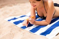 De mooie dame zonnebaadt op de handdoek op het zand bij het strand en beschermt haar handen met sunblock royalty-vrije stock foto's