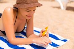 De mooie dame zonnebaadt op de handdoek op het zand bij het strand en beschermt haar handen met sunblock royalty-vrije stock foto