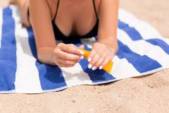De mooie dame zonnebaadt op de handdoek op het zand bij het strand en beschermt haar handen met sunblock royalty-vrije stock fotografie