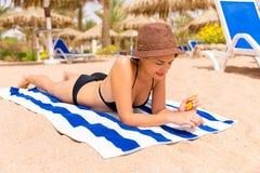 De mooie dame zonnebaadt op de handdoek op het zand bij het strand en beschermt haar handen met sunblock stock afbeelding