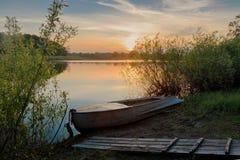 De mooie de zomerzonsondergang bij de rivier met blauwe hemel, rood en sinaasappel betrekt, groen bomen en water Stock Afbeeldingen