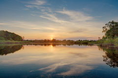 De mooie de zomerzonsondergang bij de rivier met blauwe hemel, rood en sinaasappel betrekt, groen bomen en water Stock Fotografie
