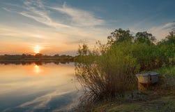 De mooie de zomerzonsondergang bij de rivier met blauwe hemel, rood en sinaasappel betrekt, groen bomen en water Royalty-vrije Stock Foto