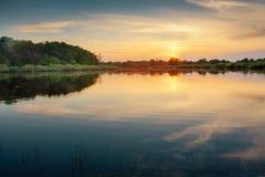 De mooie de zomerzonsondergang bij de rivier met blauwe hemel, rood en sinaasappel betrekt, groen bomen en water Stock Afbeelding