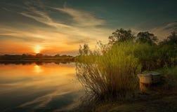 De mooie de zomerzonsondergang bij de rivier met blauwe hemel, rood en sinaasappel betrekt, groen bomen en water Royalty-vrije Stock Foto's