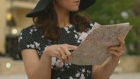 De mooie die dame met bagage en de kaart in handen werden in toevluchtstad wordt verloren, vakantie stock video