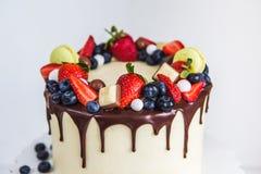 De mooie die room kleurde cake met aardbeien, bosbessen, chocolade wordt verfraaid, makaron, die zich op witte houten lijst bevin Stock Foto's
