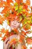 De mooie die vrouw in de herfst wordt verpakt doorbladert Stock Foto's