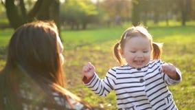 De mooie Dochter loopt aan Mamma en omhelst haar in het Park tijdens de Lente Het grappige Meisje geniet van Zonnig stock footage