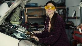 De mooie donkerbruine, autowerktuigkundige, die een GLB en een plaidoverhemd dragen, bevestigt de motor van de auto en bekeken de stock footage