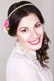 De mooie donkerbruine bruid die met natuurlijk glimlachen maakt omhoog en bloemenrozen in haar kapsel Royalty-vrije Stock Fotografie
