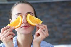 De mooie donkerbruine glimlachende vrouw eet gesneden sinaasappel Royalty-vrije Stock Afbeelding
