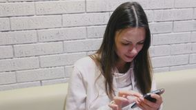 De mooie donkerbruine glimlachende vrouw typt en schuurt een bericht op mobiel telefoonzitting en wachten somebody in koffie stock videobeelden